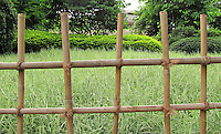 Stock photo of simple wooden fence overlooking farm.