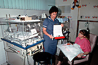 Premature infant in an high dependency intensive care cot in a special care baby unit being held for the first time by her mother. The nurse in charge of the unit is discussing the infants progress with the parent...© SHOUT. THIS PICTURE MUST ONLY BE USED TO ILLUSTRATE THE EMERGENCY SERVICES IN A POSITIVE MANNER. CONTACT JOHN CALLAN. Exact date unknown.john@shoutpictures.com.www.shoutpictures.com..