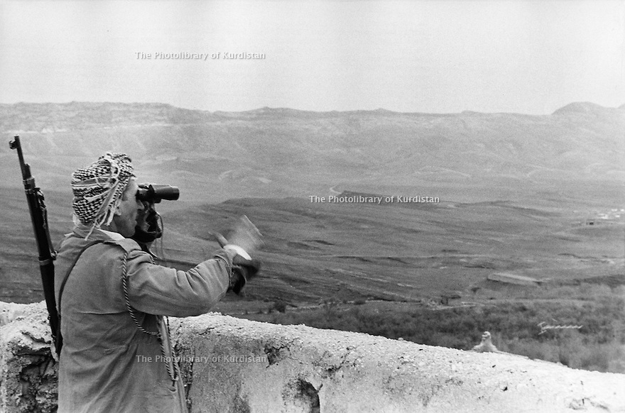 Iraq 1974 <br /> The resumption of hostilities,near Koysanjak, a peshmerga with binoculars looking at an Iraqi military camp  <br /> Irak 1974 <br /> La reprise de la lutte armée, pres de Koysanjak, un peshmerga surveillant avec des jumelles un camp militaire irakien