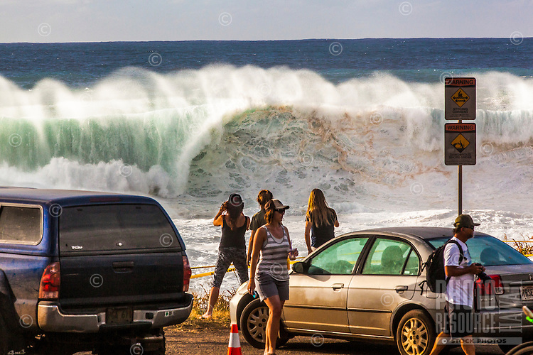 Spectators watch and take photographs of giant waves during a large winter swell at Shark's Cove, North Shore, O'ahu.
