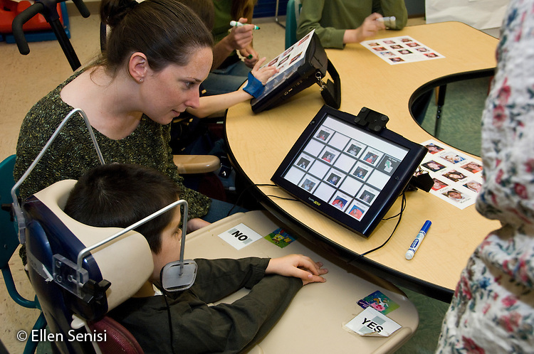MR / Albany, NY.Langan School at Center for Disability Services .Ungraded private school which serves individuals with multiple disabilities.Speech language pathologist helps student use an alternative and augmentative communication device during speech and language development lesson. Boy: 8, cerebral palsy, spastic quadriplegic, nonverbal with expressive and receptive language delays.MR: Hac2, Dub1.© Ellen B. Senisi