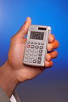 A hand holding a calculator.