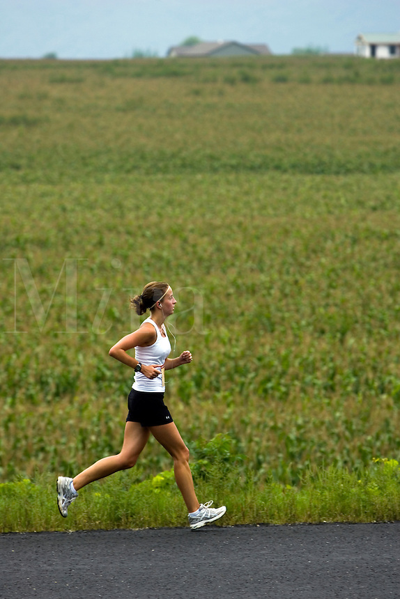 Female jogging along cornfield