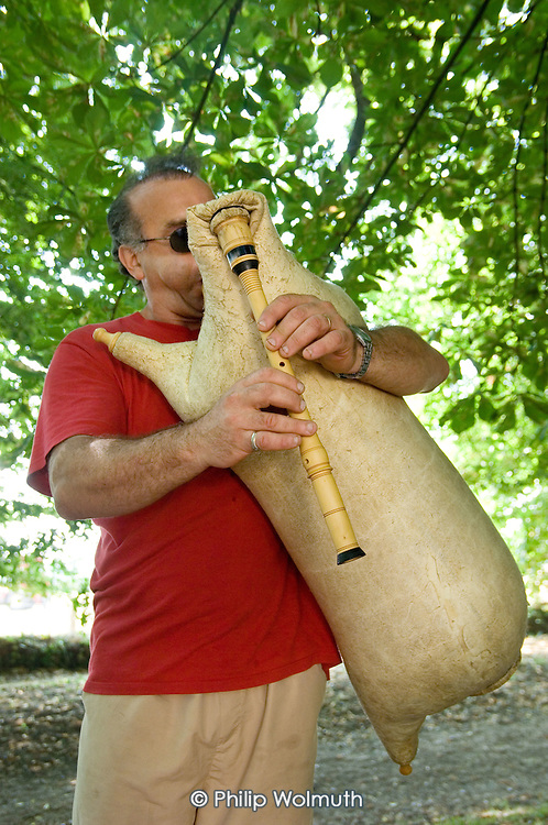 A visitor plays a goat-skin cornmuse (bagpipes) at the 31st International Festival of Luthiers and Maitres Sonneurs, in Saint Chartier, France.