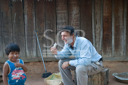 Mato Grosso State, Brazil. Xingu River. Aldeia Metuktire (Kayapo). Patrick Cunningham shaving while Bepte Txucarramae watches.