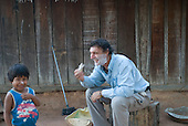 Mato Grosso State, Brazil. Xingu River. Aldeia Metuktire (Kayapo). Patrick Cunningham shaving while Bepte Txucarramae watches.