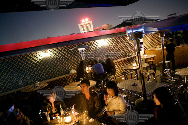 Friends spend the night out in a bar in the popular Sanlitun District.