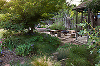 Sheltered patio with fire pit secluded behind Japanes maple in Habets backyard garden, Pleasant Hill, California