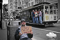Truthful Panhandler Asks For Beer Money At Union Square; Cable Car In Background With Tourists; San Francisco, C