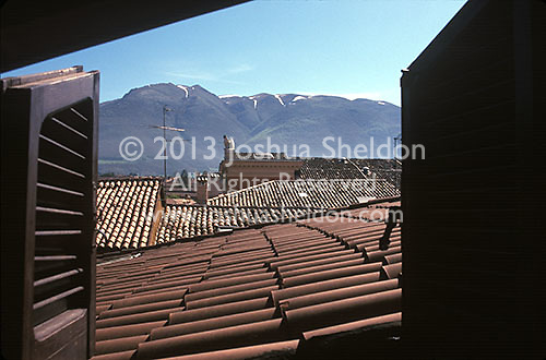 View out window of tile roof and snow topped mountains<br />