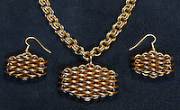"""A completed maille earring and necklace set that Michelle has titled """"Honeyscale"""", as it makes her think of honey and bees.  The necklace is a simple double cable (4-in-2) weave made out of 19 gauge 5/32"""" ID brass.  The earrings and pendant are both dragonscale weave made out of 18 gauge 1/4"""" ID bronze and 19 gauge 5/32"""" ID brass.  I love how they're glowing in this picture, thanks to diffused sunlight illuminating them from above."""