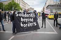 """Trotz Corona-Versammlungseinschraenkung gingen am 1. Mai 2020 in Berlin 3.000 Menschen in Berlin-Kreuzberg auf die Strasse. Sie protestierten u.a. fuer die Aufnahme von Gefluechteten aus den ueberfuellten griechischen Fluechtlingslagern und die Unterstuetzung von Automobilkonzernen wegen der Corona-Krise.<br /> Im Bild: Menschen mit einem Transparent mit der Aufschrift """"Solidarity beyond borders"""" und eine Person mit einem Schild mit der Aufschrift """"Unternehmen kriegen €$ soziale Berufe kriegen Ueberstunden"""".<br /> 1.5.2020, Berlin<br /> Copyright: Christian-Ditsch.de<br /> [NUR FUER REDAKTIONELLE ZWECKE! Werbung nur auf Anfrage beim Fotografen. Inhaltsveraendernde Manipulation des Fotos nur nach ausdruecklicher Genehmigung des Fotografen. Vereinbarungen ueber Abtretung von Persoenlichkeitsrechten/Model Release der abgebildeten Person/Personen liegen nicht vor. NO MODEL RELEASE! Don't publish without copyright Christian-Ditsch.de, Veroeffentlichung nur mit Fotografennennung, sowie gegen Honorar, MwSt. und Beleg. Konto: I N G - D i B a, IBAN DE58500105175400192269, BIC INGDDEFFXXX, Kontakt: post@christian-ditsch.de<br /> Bei der Bearbeitung der Dateiinformationen darf die Urheberkennzeichnung in den EXIF- und  IPTC-Daten nicht entfernt werden, diese sind in digitalen Medien nach §95c UrhG rechtlich geschuetzt. Der Urhebervermerk wird gemaess §13 UrhG verlangt.]"""