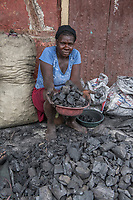 Haiti, Gros-Morne. Women selling charcoal in the market. They make about $5-$7 a day.