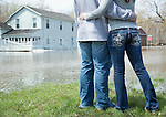 Couple looking at house surrounded by floodwaters