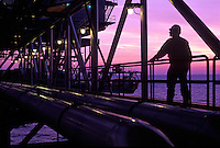 worker on offshore oil and gas production rig at dusk