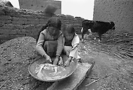 January 1979, Bolivia. Young girls working as kitchen help, clean a pig at a truck stop restaurant on the banks of the Titicaca region of Bolivia. Child labor as seen around the world between 1979 and 1980 – Photographer Jean Pierre Laffont, touched by the suffering of child workers, chronicled their plight in 12 countries over the course of one year.  Laffont was awarded The World Press Award and Madeline Ross Award among many others for his work.