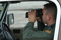 Deptartment of Homeland Security ICE Agent Noe Lopez scans the beach for illegal border crossers at the US Mexico Border in Border Fields State Park, San Diego California, the southwestern extreme of the contiguos United States Novemmber 9 2007