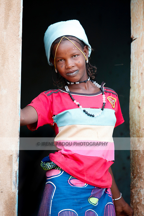 A young Fulani woman pauses in the doorframe in the town of Djibo in northern Burkina Faso.