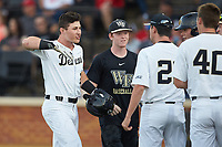 Chris Lanzilli (left) is greeted by his teammates after hitting a solo home run against the North Carolina State Wolfpack at David F. Couch Ballpark on April 18, 2019 in  Winston-Salem, North Carolina. The Demon Deacons defeated the Wolfpack 7-3. (Brian Westerholt/Four Seam Images)