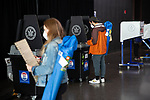 BROOKLYN, NY — OCTOBER 24, 2020:  Person wearing face masks and carrying folding chairs scan their ballots inside the Barclay's Center, during the first day of early voting in the U.S. Presidential Election, on October 24, 2020 in Brooklyn, NY.  Photograph by Michael Nagle