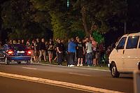 """Nach den pogromartigen Ausschreitungen gegen eine Fluechtlinsunterkunft im saechschen Heidenau am Freitag den 21. August 2015 durch Anwohnerinnen der Ortschaft, kamen am Samstag de 22. August 2015 ca. 250 Menschen in die Ortschaft um ihre Solidaritaet mit den Gefluechteten zu zeigen.<br /> Am Vorabend hatten Rassisten, Nazis und Hooligans sich zum Teil Strassenschlachten mit der Polizei geliefert um zu verhindern, dass Fluechtlinge in einen umgebauten Baumarkt einziehen. Ueber 30 Polizisten wurden dabei verletzt.<br /> Bis in die Abendstunden des 22. August blieb es trotz spuerbarer Anspannung um die Unterkunft ruhig. Im Laufe des Tages wurden immer wieder Gefluechtete mit Reisebussen gebracht was von den wartenenden Heidenauern mit Buh-Rufen begleitet wurde. Vereinzelt wurde auch """"Sieg Heil"""" gerufen, was die Polizei jedoch nicht verfolgte.<br /> Kurz vor 23 Uhr griffen Nazis und Hooligans wie am Vorabend die Polizei mit Steinen, Flaschen, Feuerwerkskoerpern und Baustellenmaterial an. Die Polizei mussten mehrfach den Rueckzug antreten, scheuchte den Mob dann von der Fluechtlingsunterkunft weg. Dabei wurden auch wieder Traenengasgranaten verschossen. Mindestens ein Nazi wurde festgenommen.<br /> Im Bild: Die Rechten haben sich in der Naehe der Unterkunft fuer die Gefluechteten versammelt und warten, """"dass es losgeht"""".<br /> 22.8.2015, Heidenau/Sachsen<br /> Copyright: Christian-Ditsch.de<br /> [Inhaltsveraendernde Manipulation des Fotos nur nach ausdruecklicher Genehmigung des Fotografen. Vereinbarungen ueber Abtretung von Persoenlichkeitsrechten/Model Release der abgebildeten Person/Personen liegen nicht vor. NO MODEL RELEASE! Nur fuer Redaktionelle Zwecke. Don't publish without copyright Christian-Ditsch.de, Veroeffentlichung nur mit Fotografennennung, sowie gegen Honorar, MwSt. und Beleg. Konto: I N G - D i B a, IBAN DE58500105175400192269, BIC INGDDEFFXXX, Kontakt: post@christian-ditsch.de<br /> Bei der Bearbeitung der Dateiinformationen darf die Urheberkennzeich"""