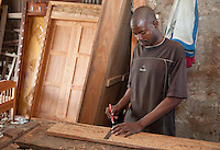 Zanzibar, Tanzania.  A Woodcarver Measures as he Prepares to Chisel a Design in a Door Side Panel.