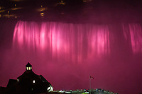 Famous, amazing Niagara Falls night view with its water lit up in pink and the Table Rock Welcome Center in the foreground, USA and Canada
