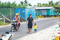A mother and child walk along a road in central Funafuti, Tuvalu. Located in the South West Pacific Ocean, Tuvalu is the world's 4th smallest country and is one of the most vulnerable to climate change impacts including sea level rise, drought and extreme weather events. Tuvalu - March, 2019.