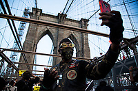 NEW YORK, USA - May 25: A man goes live from his cell phone on the Brooklyn Bridge on the first anniversary of death on May 25, 2021 in New York City. George Floyd's assassination in Minneapolis sparked a worldwide outcry and continued to propel the Black Lives Matter movement through different cities in the United States and the world. (Photo by Pablo Monsalve / VIEWpress via Getty Images)