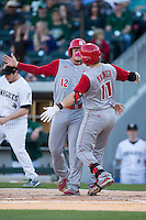 Andrew Knizner (11) of the North Carolina State Wolfpack gets a hug from teammate Preston Palmeiro (12) after hitting a home run against the Charlotte 49ers at BB&T Ballpark on March 31, 2015 in Charlotte, North Carolina.  The Wolfpack defeated the 49ers 10-6.  (Brian Westerholt/Four Seam Images)