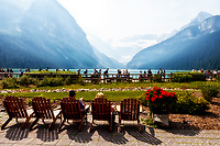 Muskoka chairs at Lake Louise with a scenic view of the BC forest fire smoke in the mountains.