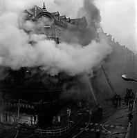 """Edifice commercial et de bureaux, magasin """"Au gaspillage"""" au début du XXe siècle, """"Au bon marché de Paris, """"le Printemps"""" et les assurances """"Le continent"""" dans les années 1960, """"Bouchara"""", """"Zara"""", 47 rue d'Alsace-Lorraine. 11 Mars 1964. Vue de l'incendie de l'immeuble du Printemps et de l'intervention des pompiers : vue prise au niveau de la rue ; l'immeuble ravagé par le feu, entouré de nuages de fumée épaisse, des lances à incendie dont deux dirigées depuis le sol vers le premier étage, la grande échelle au second plan."""