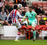 11th September 2021;  Bet365 Stadium, Stoke, Staffordshire, England; EFL Championship football, Stoke City versus Huddersfield Town; Matty Pearson of Huddersfield Town chips the ball over Romaine Sawyers of Stoke City