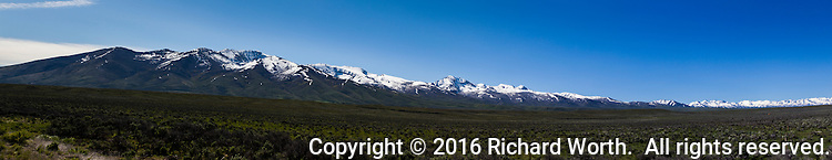 Snow covered peaks rise over sagebrush covered high desert in northern Nevada.