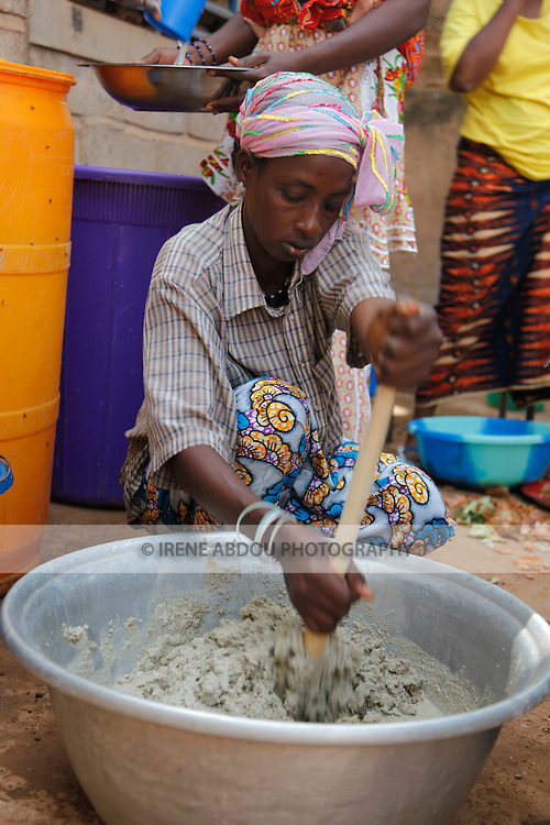 In Burkina Faso, West Africa, Muslim families celebrate the birth of a child on the 7th day after birth.  Women throughout Ouagadougou - friends and family - congregate at the mother's house on the morning of the baptism to help cook for guests.  Here, a woman stirs pounded millet with water to make a traditional millet drink.