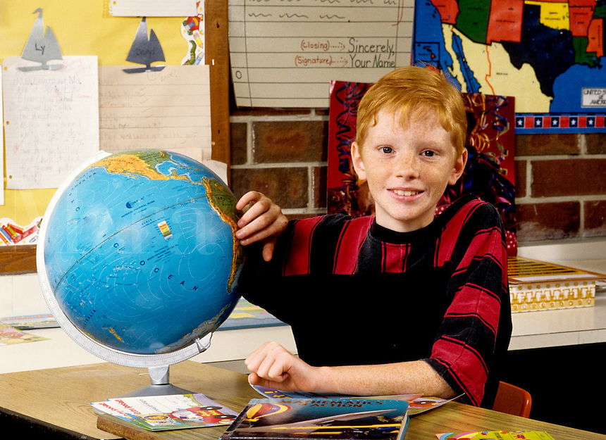 boy age 11 in sixthth grade learning from globe about the worl