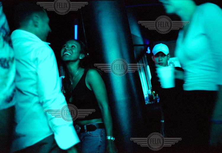 A westerner flirting with a Thai girl in a trendy bar in Bangkok.