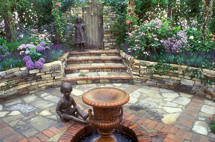 English Secret Garden. Outdoor room, sunken stone patio with child statues and stone walls, lush gardens. Designed by Paul Stone. Circular brick and stone landscaping, lush flowers, children ornaments, bird bath, wall, hidden and private, sense of enclosure