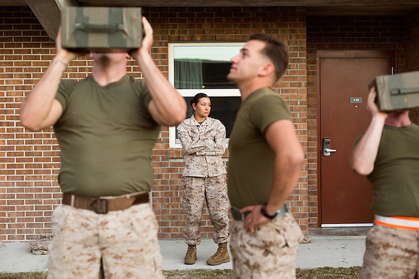 October 22, 2014. Camp LeJeune, North Carolina.<br />  Cpl. Raquel Mathieu, age 22, center, watches as other Marines of the Ground Combat Element Integrated Task Force conduct the 30 lbs. ammunition box lift portion of the Combat Fitness Test (CFT). The CFT includes a half mile run, followed by a series of timed physical tests that simulate conditions they could encounter in combat situations.<br />  The Ground Combat Element Integrated Task Force is a battalion level unit created in an effort to assess Marines in a series of physical and medical tests to establish baseline standards as the Corps analyze the best way to possibly integrate female Marines into combat arms occupational specialities, such as infantry personnel, for which they were previously not eligible. The unit will be comprised of approx. 650 Marines in total, with about 400 of those being volunteers, both male and female. <br />  Jeremy M. Lange for the Wall Street Journal<br /> COED