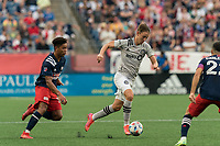 FOXBOROUGH, MA - JULY 25: Lassi Lappalainen #21 of CF Montreal dribbles as Brando Bye #15 of New England Revolution defends during a game between CF Montreal and New England Revolution at Gillette Stadium on July 25, 2021 in Foxborough, Massachusetts.