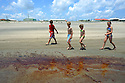Children walk along the public beach just before officials closed the beaches as oil washed on shore at Grand Isle, La., Friday, May 21, 2010.