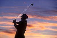 Silhouette of a golfer following his drive.