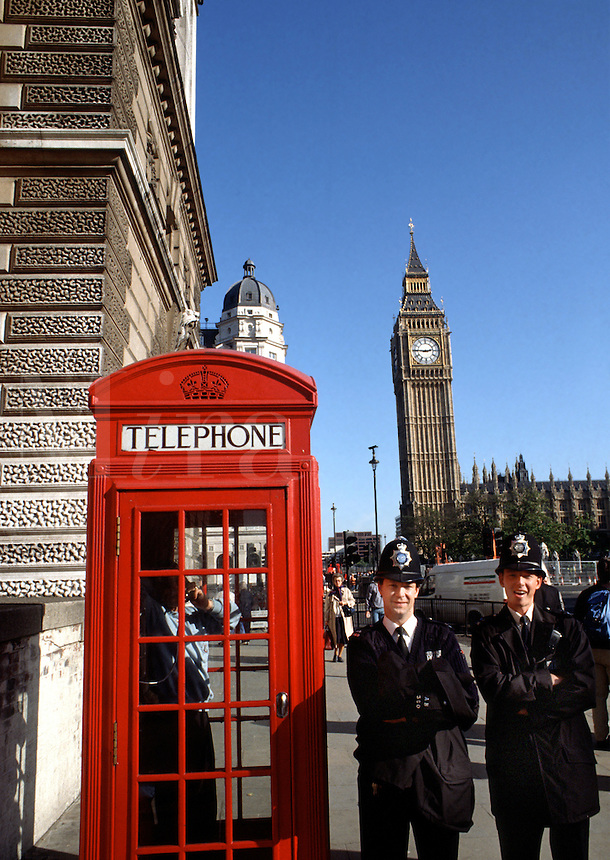 Smiling Bobbies pose in front of a telephone box with Big Ben and the British Parliament building in the background. London, England.