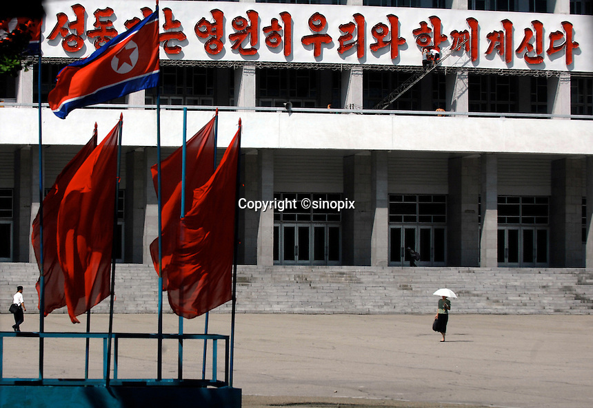 """People pass a Government building in Pyongyang, North Korea. The DPRK (Democratic People's Republic of Korea) is the last great dictatorship where the people are bombarded with images of the """"Eternal President"""" Kim Il-sung who died in 1994 and his son and current leader Kim Jong-il who are worshipped like a God."""