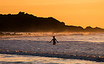 A lone swimmer leaves the water after her swim in the sea which is bathed in the golden glow of sunrise at Langland Bay near Swansea this morning.