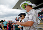 ARLINGTON HEIGHTS, IL - AUGUST 12: A man dressed in a money themed hat looks through the day's program on Arlington Million Day at Arlington Park on August 12, 2017 in Arlington Heights, Illinois. (Photo by Jon Durr/Eclipse Sportswire/Getty Images)