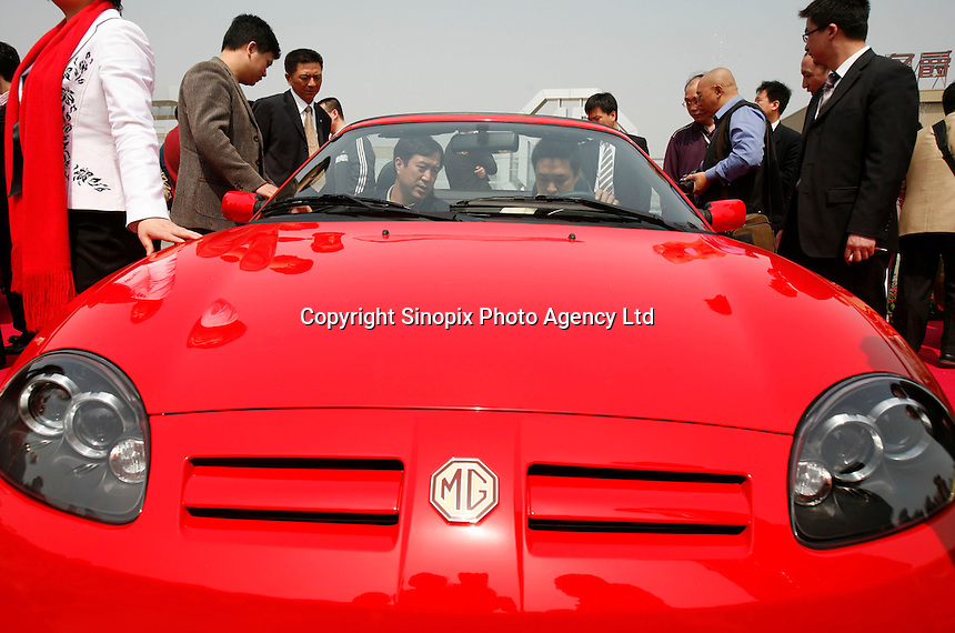 Guests sit in a newly launched MG  model at the Nanjing MG Automibile Corporation plant in Nanjing, China. The Chinese company is now in a position to take on Rover's assets and plan its future. It intended to relocate the engine plant and some car production plant to China but to retain some car production plant in the UK..27 Mar 2007