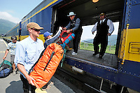 Nic Moir hands a dry bag to the Brakeman Tony xxx. The Alaska Railroad's Spencer Glacier Whistlestop train gives visitors access to hiking, camping and stunning views.