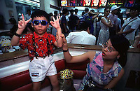 A mother and her son eat ice-cream on a oark bench in guangzhou, China.  China's one child policy has resulted in a nation of spoilt children, where boys outnumber gils by almost 20 in every hundred.<br /> ©sinopix