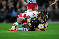 Chris Wyles of Saracens forces his way past Marland Yarde of Harlequins to score a try